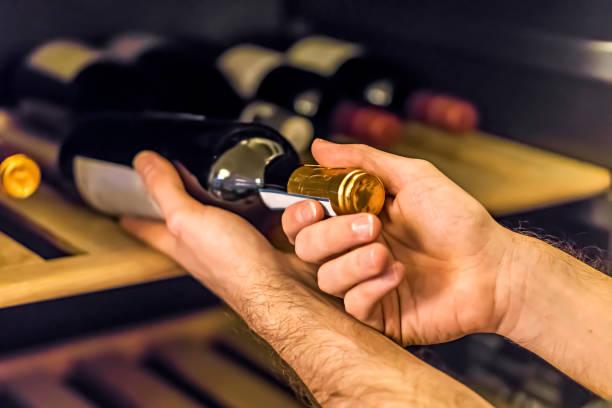 Homme qui sort une bouteille de vin de sa cave à vins