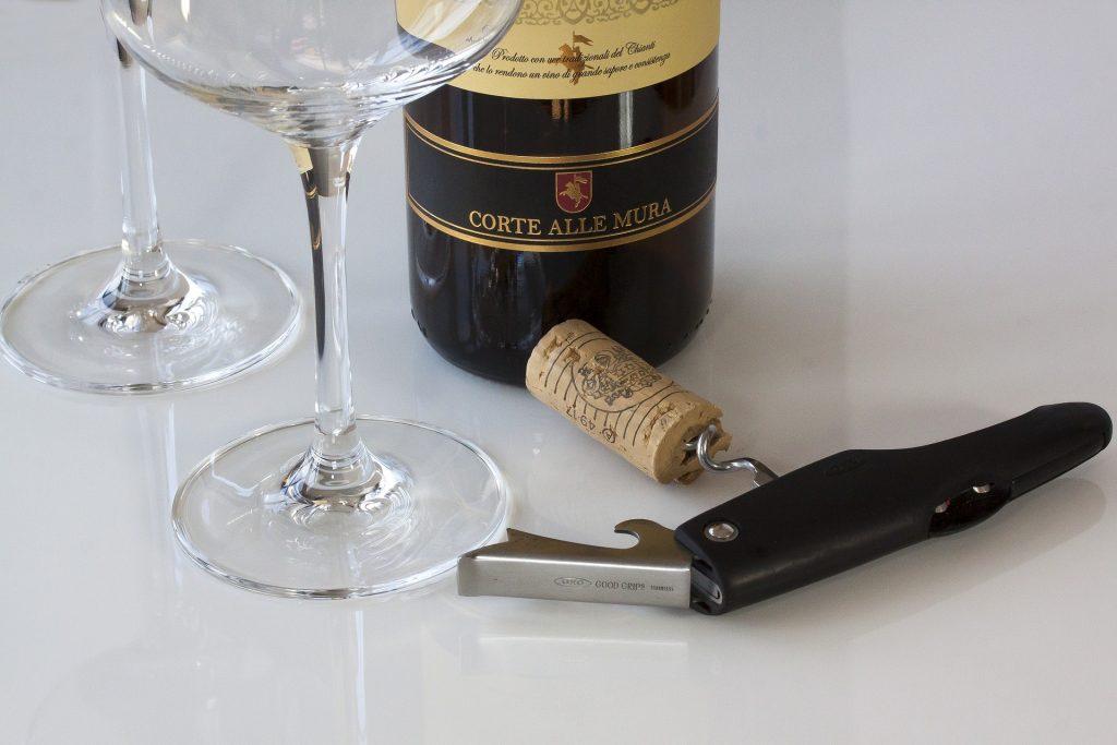 Une bouteille de vin avec deux verre à pied et un tire-bouchon