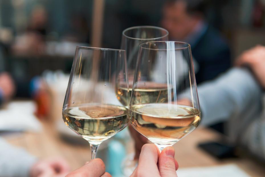 Amis en train de trinquer avec des verres de vin blanc